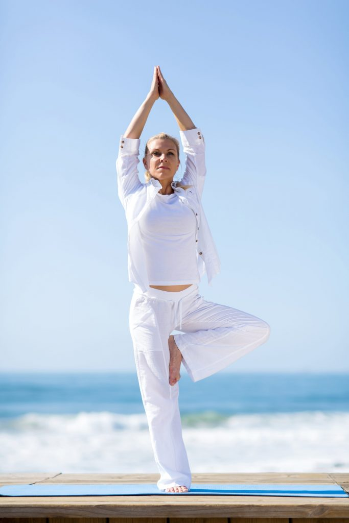 woman in white doing a yoga pose at the beach